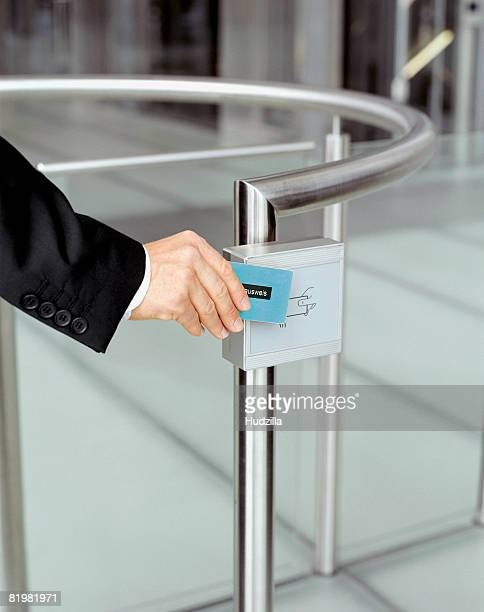 Businessman swiping identification at security gate