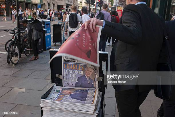 A businessman takes a free newspaper with the headline featuring a portrait of Prince Charles the Londoner of the decade according to the Evening...