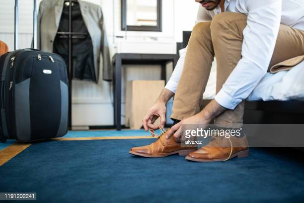 businessman takes off his shoe in hotel room - absence stock pictures, royalty-free photos & images