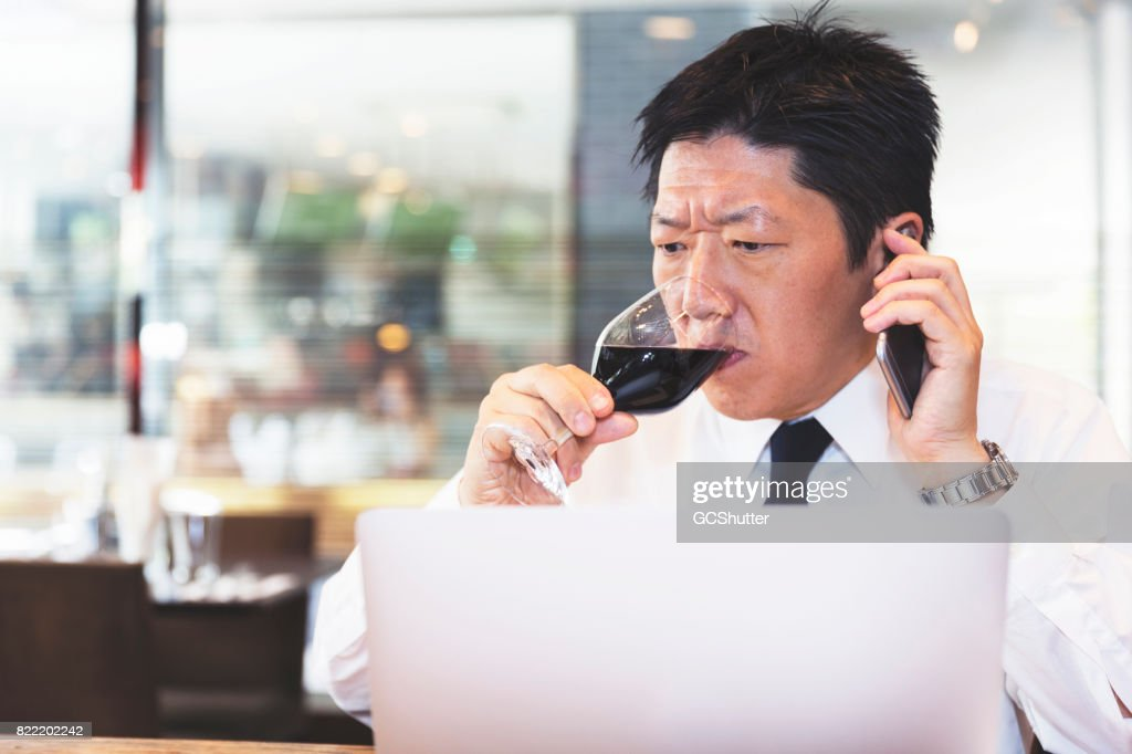 Businessman taking a large drink of his glass of wine while on the phone with a colleague : Stock Photo
