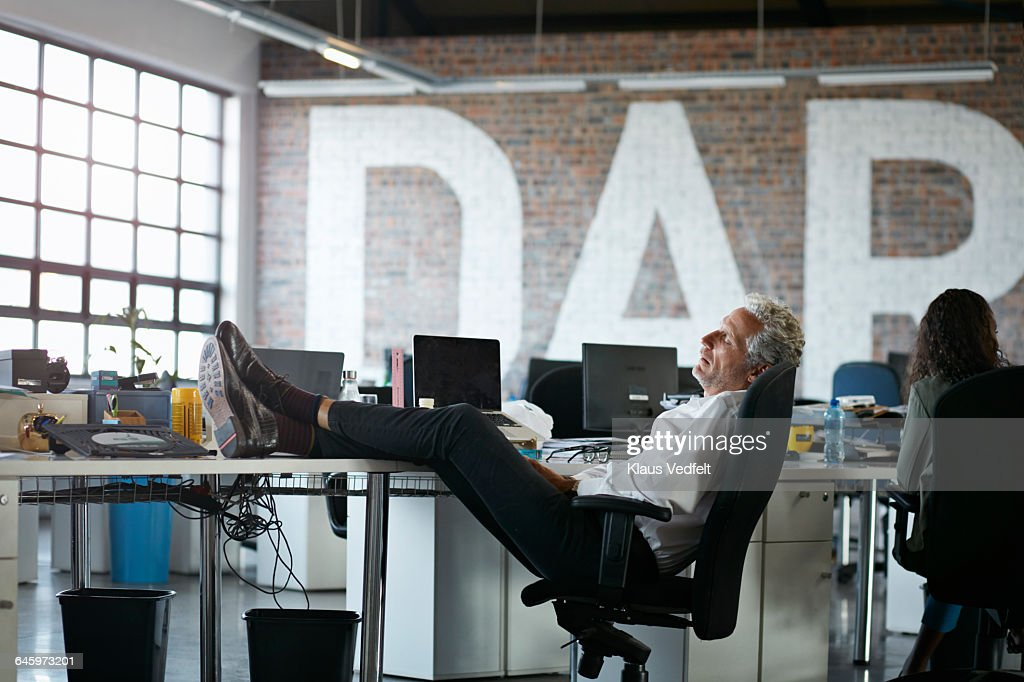 Businessman taking a nap, at big open office : Stock Photo