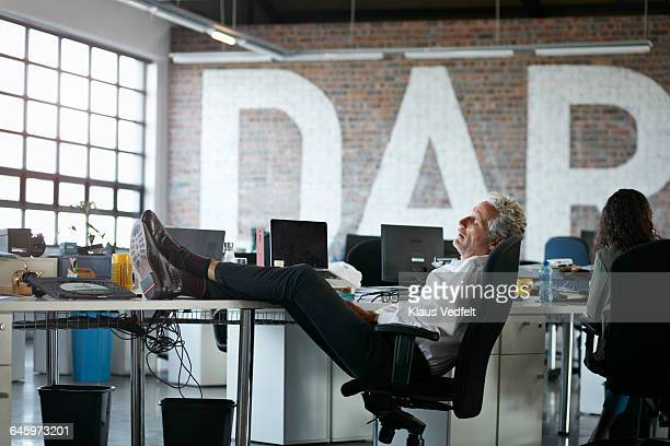 businessman taking a nap, at big open office - wasting time stock pictures, royalty-free photos & images