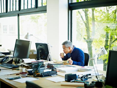 Businessman taking bite of sandwich at desk - gettyimageskorea