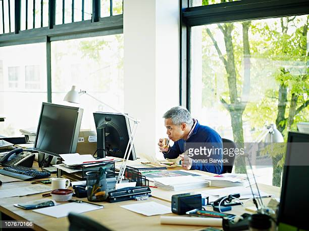 Businessman taking bite of sandwich at desk