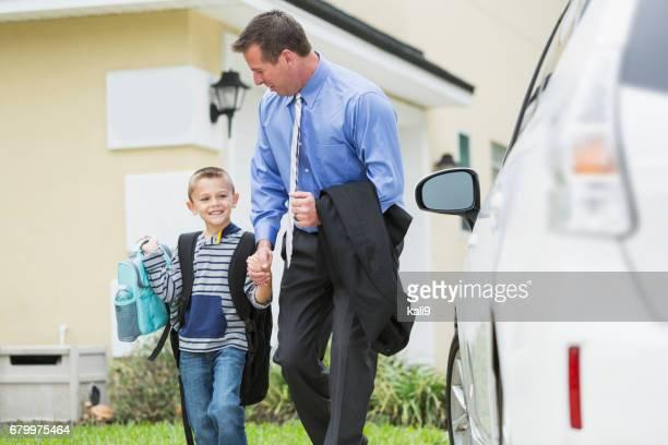 Businessman taking boy to school, walking to car