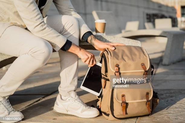 businessman taking digital tablet out of backback, partial view - sac à dos photos et images de collection