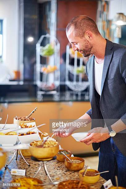 Businessman taking food from breakfast buffet