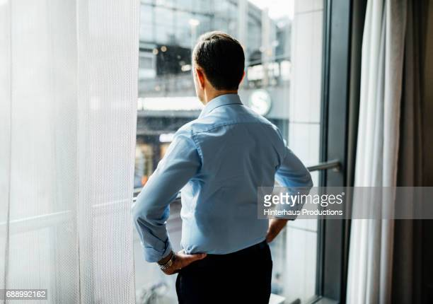 Businessman Taking In The View from His Hotel Room