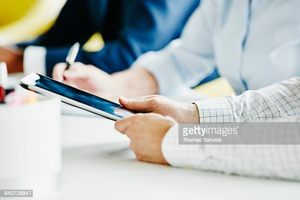 Businessman taking notes on digital tablet