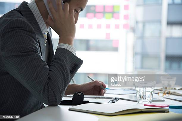 Businessman taking notes while the phone