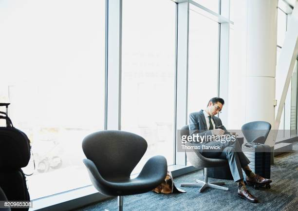 Businessman taking notes while waiting for flight in airport
