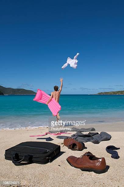 Homme d'affaires de décoller les vêtements et courir sur l'océan