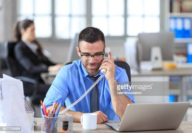 Businessman taking on phone at work