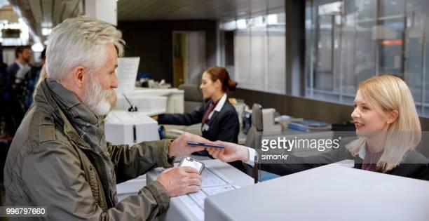 passeport prenant homme d'affaires de préposé au comptoir des billets - hygiaphone photos et images de collection