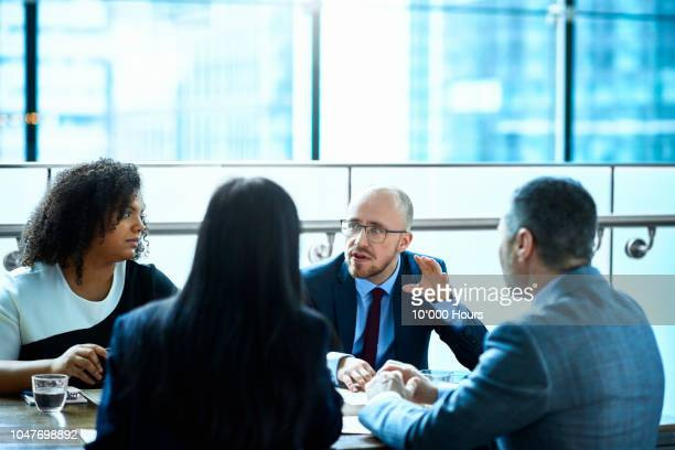 businessman talking and gesturing to colleagues in meeting - formal stock pictures, royalty-free photos & images