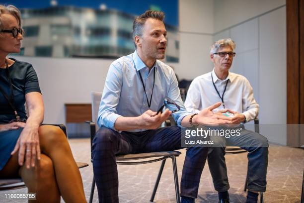 businessman talking during panel discussion - podiumsdiskussion stock-fotos und bilder