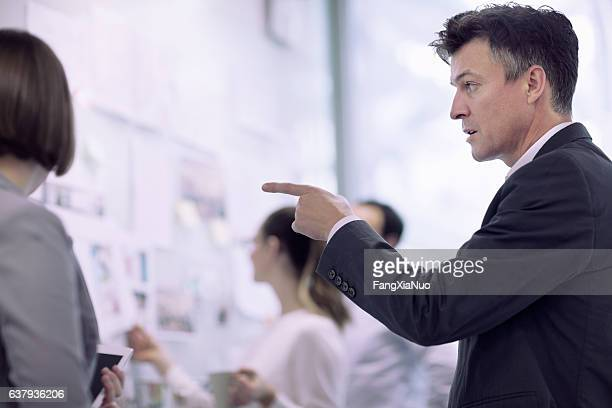 businessman talking in meeting with planning colleagues - copyright stock photos and pictures
