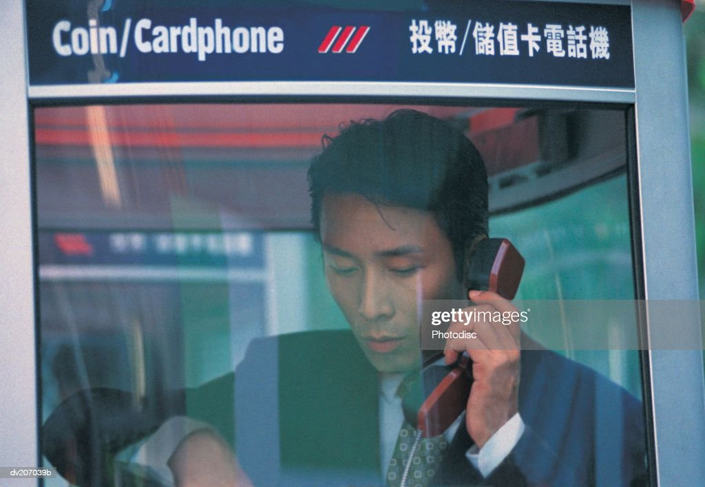 Businessman talking in phonebooth : Stock Photo