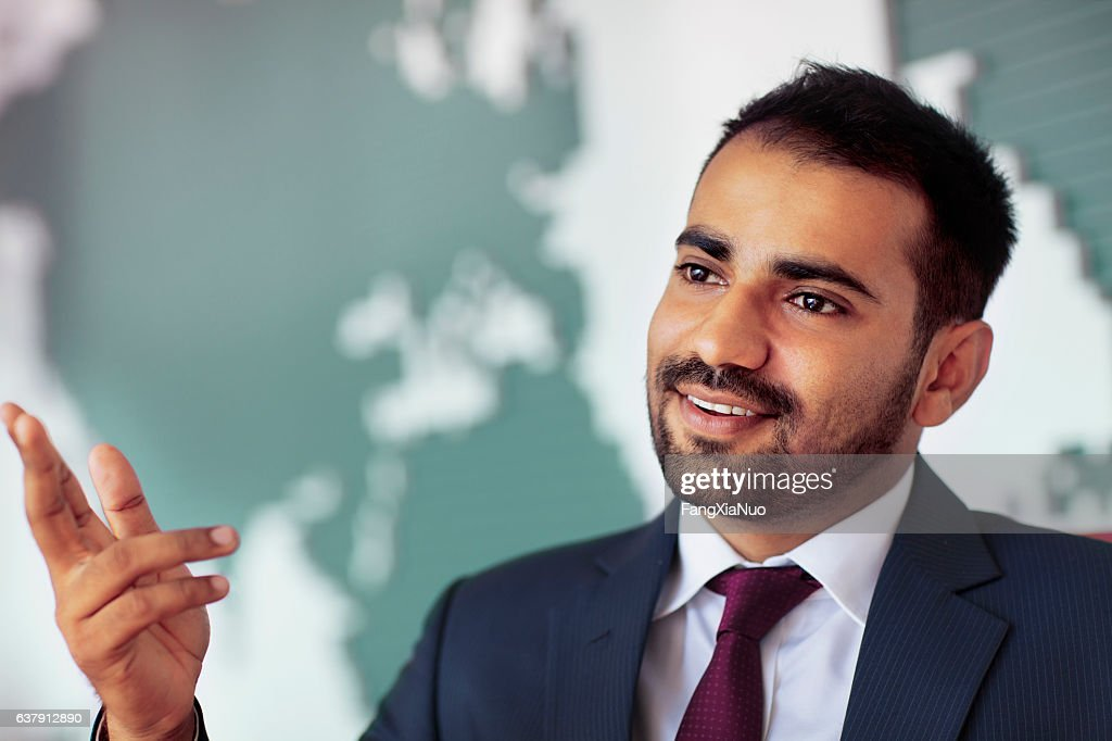 Businessman talking in room with map on wall : Stock Photo