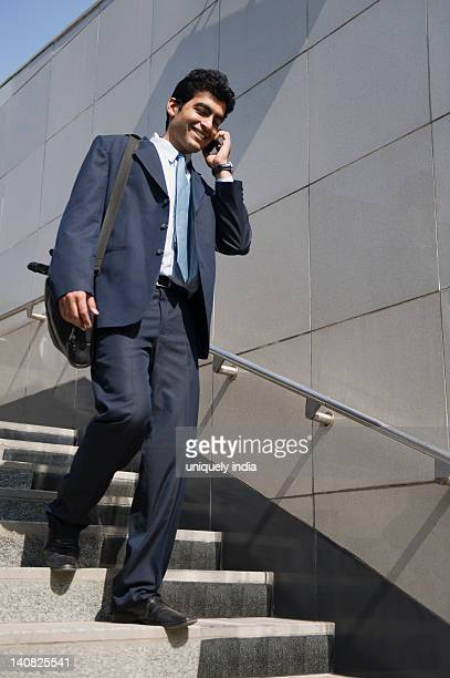 Businessman talking on a mobile phone and moving down stairs to subway, Gurgaon, Haryana, India