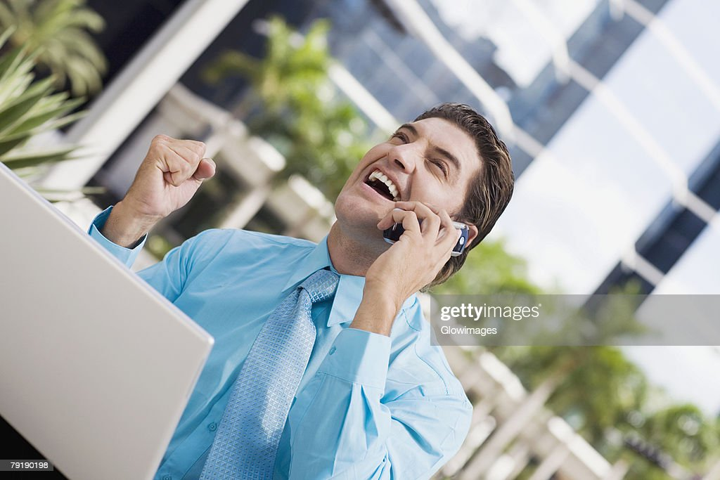Businessman talking on a mobile phone and raising his fist in front of a laptop : Stock Photo