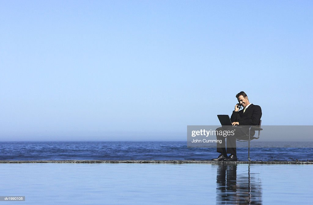 Businessman Talking on a Mobile Phone and Using a Laptop Computer by the Sea : Stock Photo