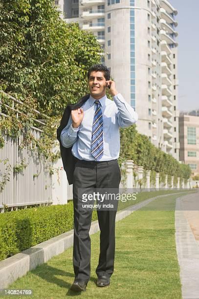 Businessman talking on a mobile phone at a sidewalk, Gurgaon, Haryana, India