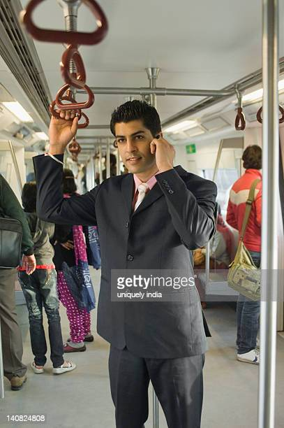 Businessman talking on a mobile phone in a subway train, New Delhi, India
