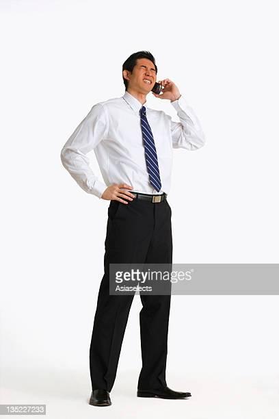 businessman talking on a mobile phone - mano sul fianco foto e immagini stock