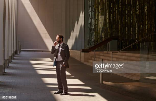 Businessman talking on a phone outside the office