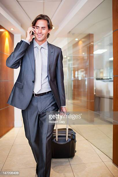 Businessman talking on cell phone and pulling suitcase