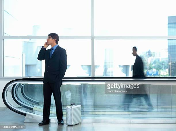 Businessman talking on cell phone by airport escalator