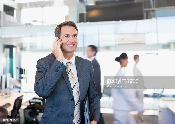 businessman talking on cell phone in busy office - northern european stock photos and pictures