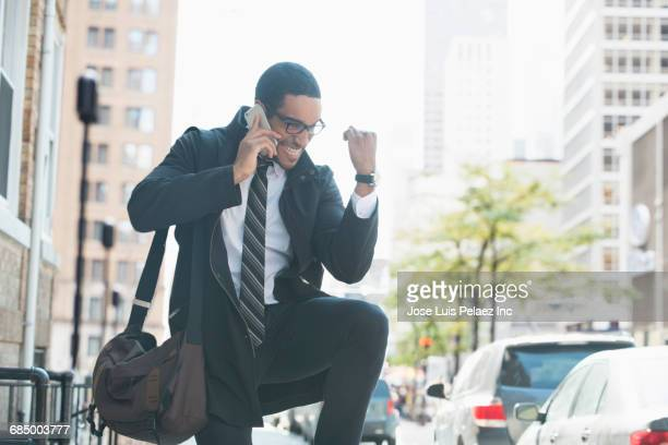 businessman talking on cell phone in city and celebrating - punching the air stock pictures, royalty-free photos & images