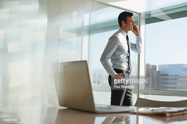 businessman talking on cell phone in office - overhemd en stropdas stockfoto's en -beelden
