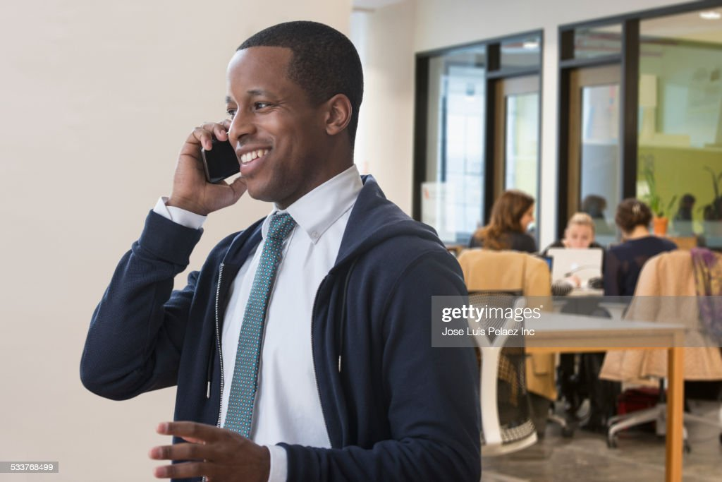 Businessman talking on cell phone in office : Foto stock