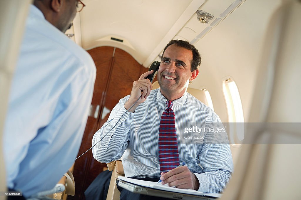 Businessman talking on cell phone in private jet : Stockfoto