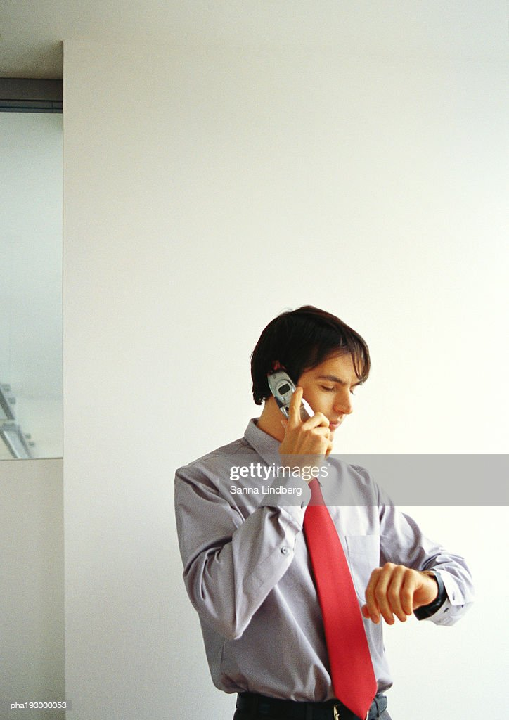 Businessman talking on cell phone, looking down at watch. : Stockfoto