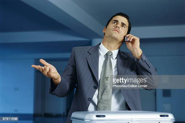 businessman talking on cell phone, making frustrated gesture with hand - impatient stock pictures, royalty-free photos & images