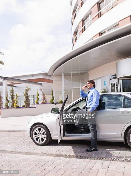 Businessman talking on cell phone next to car