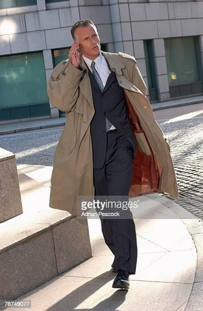 businessman talking on cell phone - トレンチコート ストックフォトと画像