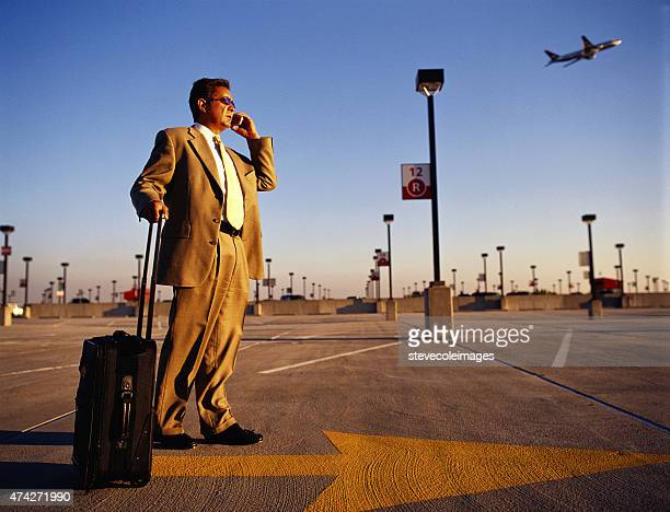 Businessman talking on cell phone waiting at airport.