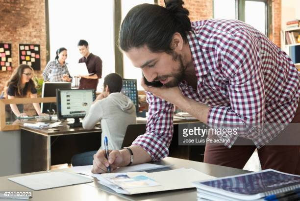 Businessman talking on cell phone writing on paperwork