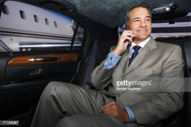 businessman talking on his cell phone in limo - limousine stock pictures, royalty-free photos & images
