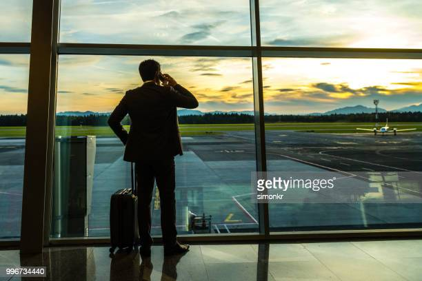 businessman talking on mobile phone at airport - premium access stock pictures, royalty-free photos & images