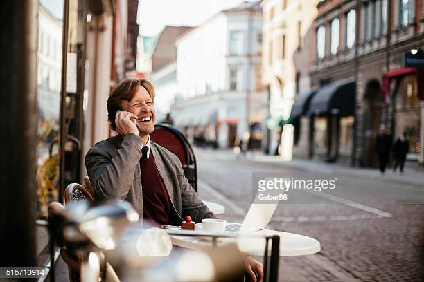 Businessman talking on mobile phone in cafe