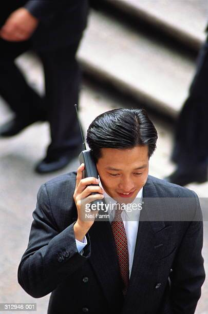 Businessman talking on mobile phone outdoors, elevated view