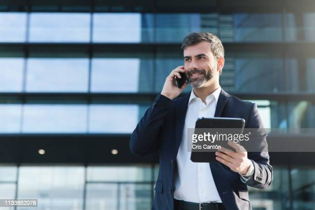 businessman talking on mobile phone - cris cantón photography fotografías e imágenes de stock