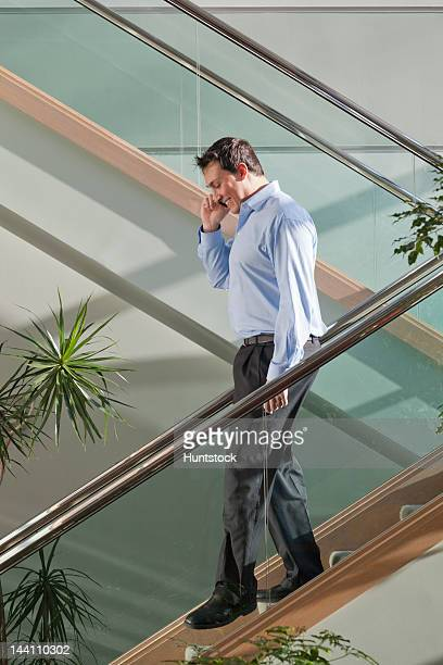 Businessman talking on mobile phone walking down stairs