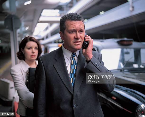 businessman talking on mobile phone with woman standing behind him